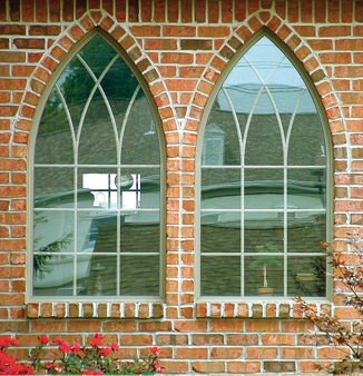 Two windows side by side in a brick facade: Cathedral window shape with gothic grids.